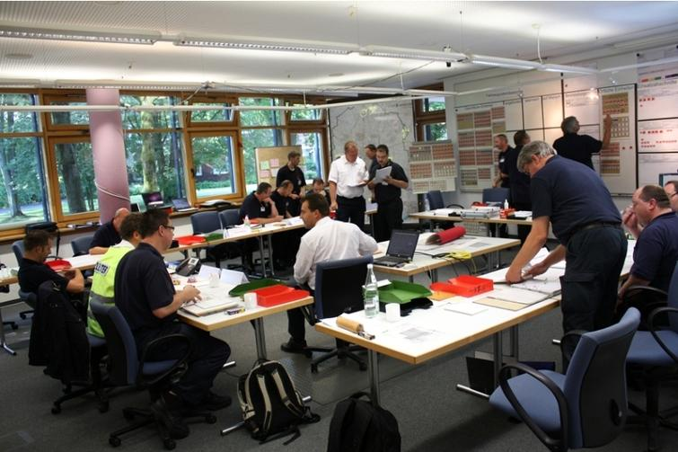 """Staff exercise at State Fire Service Institute North Rhine-Westphalia. The case study's goal is to recognize the interactions between staff members and objects – in this image: """"conversation"""" (left/center), """"analyzing a document together"""" (top center), and """"editing a display"""" (top right)."""
