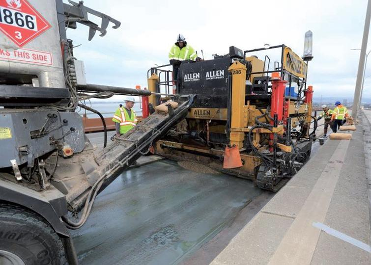A continuous volumetric mixing/batching truck discharging polyester concrete into the paver (Courtesy of John Huseby, Caltrans).