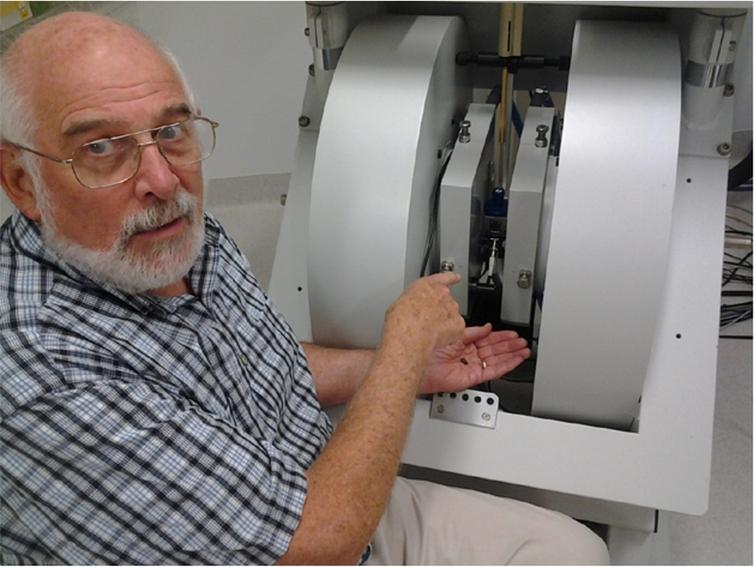 Larry Berliner working at the Bruker L-band/X-band in-vivo imaging spectrometer at the Centre for Advanced Imaging, University of Queensland. He is holding a coffee bean which was imaged at X-band on the basis of its paramagnetic radical content.
