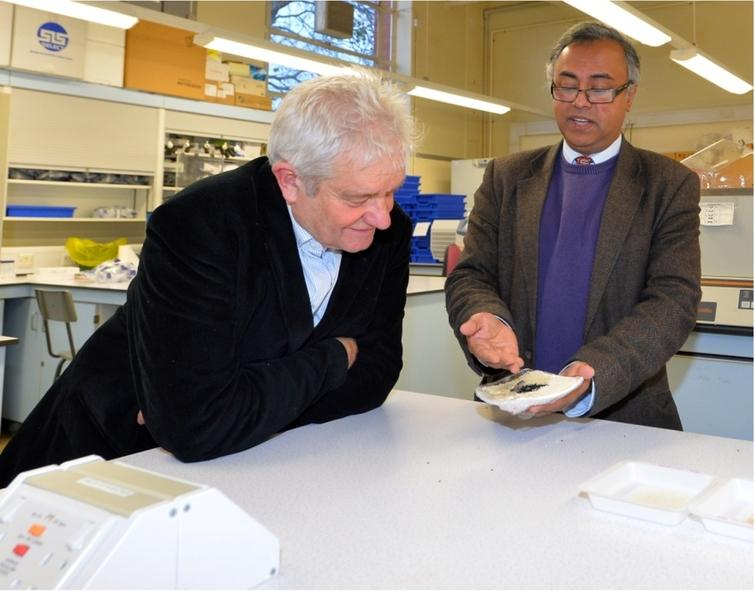 Nobel laureate, Sir Paul Nurse FRS (left), with the author of this article (6 December 2017). Sir Paul Nurse is looking at Bangladeshi aromatic rice (Kalijeera, considered to be the smallest rice in the world) and Nigella sativa seeds (known as Kalijeera in Bengali and after which the Kailjeera variety of Bangladeshi aromatic rice is named). Sir Paul Nurse officially opened the Laboratory of Biomedical and Environmental Health Research which carries out interdisciplinary research with spectroscopic techniques playing a central role. Photo credit: Alex Hannam.
