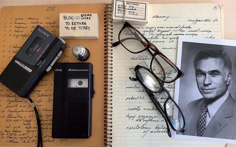 Some memorabilia from Bob Terry's office at UCSD. His notebook, tape recorders, glasses, epon blocks for electron microscopy of Alzheimer's disease brain biopsies from where the images of paired helical filaments were obtained, and a picture of him at his time at the Albert Einstein College of Medicine.