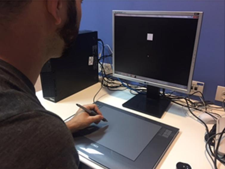 The Reach Test. Shown here is an illustration of the experimental setup during the reach test, administered before and after the exercise set. The participant is holding a stylus above a digitizing tablet. He hovers the stylus at a small distance above the tablet from a starting position to a target shown on the screen as a white square. At the end of the reaching movement, the trace of the movement is shown on the screen. Written approval for use of these pictures for publication was obtained from the person photographed.